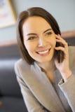 Mujer bastante joven en el teléfono en barra de café Foto de archivo libre de regalías