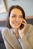 Mujer bastante joven en el teléfono en barra de café Foto de archivo