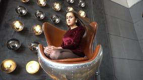 Mujer bastante joven en el vestido que se sienta en la butaca y actitudes en estudio metrajes