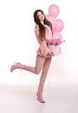Mujer bastante joven en flores color de rosa de la tenencia rosada en caja del sombrero encima Imagen de archivo libre de regalías