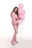 Mujer bastante joven en flores color de rosa de la tenencia rosada en caja del sombrero encima Fotos de archivo libres de regalías