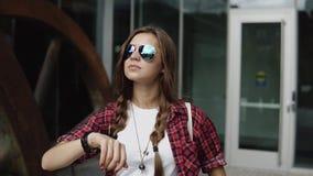 Mujer bastante joven en gafas de sol elegantes y camisa roja en una jaula que comprueba tiempo en su reloj cerca de la entrada de almacen de metraje de vídeo