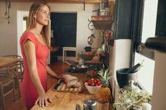 Mujer bastante joven en la cocina que mira lejos Imagenes de archivo