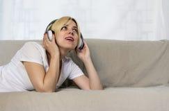 Mujer bastante joven en los auriculares que mienten en música que escucha del sofá o el libro audio con los ojos cerrados Señora  Foto de archivo