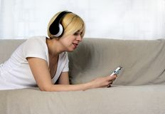 Mujer bastante joven en los auriculares que mienten en música que escucha del sofá o el libro audio con los ojos cerrados Señora  Imagenes de archivo