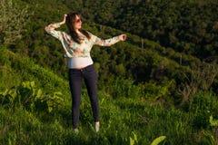 Mujer bastante joven en montañas el tiempo de la puesta del sol Imágenes de archivo libres de regalías