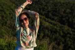 Mujer bastante joven en montañas el tiempo de la puesta del sol Fotos de archivo