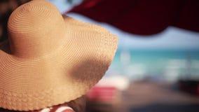 Mujer bastante joven en sombrero y gafas de sol que sonríe mientras que ella está en una playa soleada 1920x1080 almacen de video