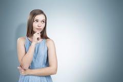 Mujer bastante joven en un pensamiento azul del vestido Fotografía de archivo libre de regalías