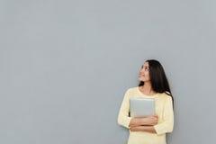 Mujer bastante joven feliz que sostiene el ordenador portátil y que mira lejos Fotografía de archivo libre de regalías