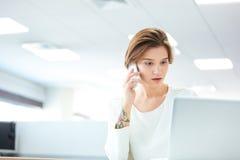 Mujer bastante joven pensativa que habla en el teléfono celular en oficina Fotos de archivo