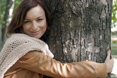 Mujer bastante joven que abraza el árbol en un parque Imagen de archivo