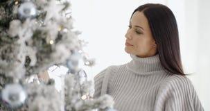 Mujer bastante joven que adorna su árbol de navidad Imágenes de archivo libres de regalías
