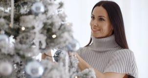 Mujer bastante joven que adorna su árbol de navidad Fotografía de archivo libre de regalías
