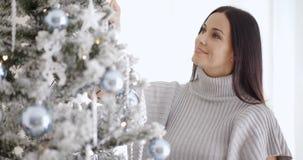 Mujer bastante joven que adorna su árbol de navidad Fotos de archivo libres de regalías