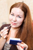 Mujer bastante joven que aplica el lápiz labial rosado Fotos de archivo libres de regalías