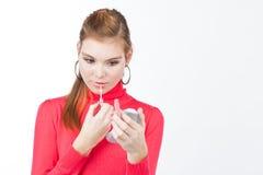 Mujer bastante joven que aplica lustre del labio Imagenes de archivo