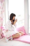 Mujer bastante joven que bebe su café de la mañana Fotos de archivo