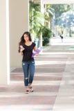 Mujer bastante joven que camina al aire libre mandando un SMS en el teléfono elegante Imagen de archivo