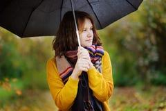 Mujer bastante joven que camina en el tiempo nublado lluvioso del otoño Imágenes de archivo libres de regalías