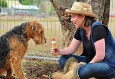 Mujer bastante joven que comparte el helado con el perro Imagen de archivo libre de regalías