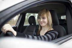 Mujer bastante joven que conduce su nuevo coche Imagenes de archivo