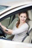 Mujer bastante joven que conduce su nuevo coche Fotos de archivo libres de regalías