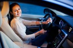 Mujer bastante joven que conduce su nuevo coche Imágenes de archivo libres de regalías