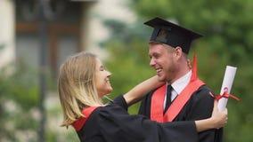 Mujer bastante joven que da beso blando al novio, par feliz de graduados almacen de video