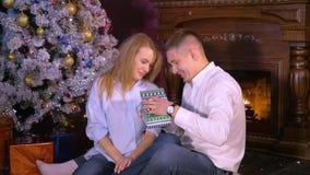 Mujer bastante joven que da a un actual ti su novio cerca de la chimenea de la Navidad HD almacen de video