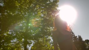 Mujer bastante joven que da vuelta a una cámara en parque almacen de video