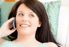 Mujer bastante joven que habla en el teléfono que miente en el sofá Imagenes de archivo