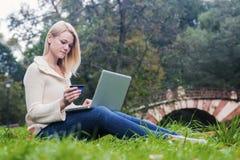 Mujer bastante joven que hace compras en línea usando tarjeta de crédito y el ordenador portátil en parque Foto de archivo libre de regalías