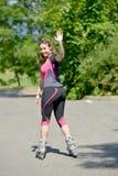 Mujer bastante joven que hace el rollerskate en una pista foto de archivo