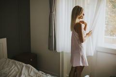 Mujer bastante joven que hace una pausa la ventana Imágenes de archivo libres de regalías