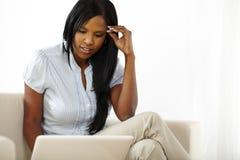Mujer bastante joven que hojea en la computadora portátil Foto de archivo libre de regalías