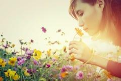 Mujer bastante joven que huele las flores Foto de archivo libre de regalías