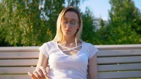 Mujer bastante joven que lee un libro en el banco al aire libre en la puesta del sol metrajes