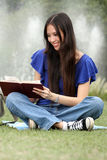 Mujer bastante joven que lee un libro en el parque Fotografía de archivo