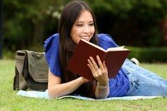 Mujer bastante joven que lee un libro en el parque Imagen de archivo