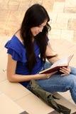 Mujer bastante joven que lee un libro en la escalera Fotos de archivo libres de regalías