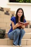 Mujer bastante joven que lee un libro en la escalera Foto de archivo