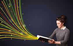 Mujer bastante joven que lee un libro mientras que las líneas coloridas son comin Fotografía de archivo libre de regalías