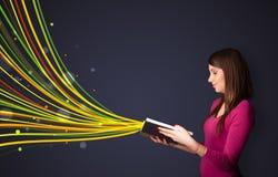 Mujer bastante joven que lee un libro mientras que las líneas coloridas son comin Fotografía de archivo