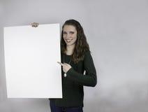 Mujer bastante joven que lleva a cabo la muestra en blanco Fotos de archivo