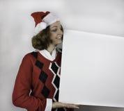 Mujer bastante joven que lleva el sombrero de Papá Noel que lleva a cabo la muestra en blanco Fotos de archivo