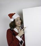 Mujer bastante joven que lleva el sombrero de Papá Noel y que lleva a cabo la muestra en blanco Imagenes de archivo