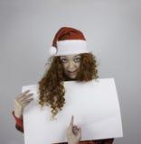 Mujer bastante joven que lleva el sombrero de Papá Noel y que lleva a cabo la muestra en blanco Foto de archivo libre de regalías
