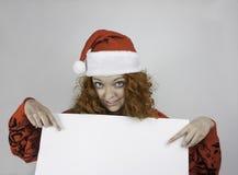 Mujer bastante joven que lleva el sombrero de Papá Noel y que lleva a cabo la muestra en blanco Imagen de archivo libre de regalías