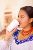 Mujer bastante joven que lleva la blusa andina tradicional, colocando el café para arriba de consumición de la taza blanca Imagen de archivo libre de regalías
